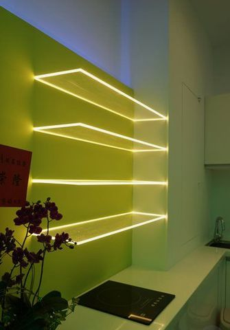 A neon green painted wall with glass shelves that glow.