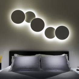 Panel lights are mounted to metal art pieces and hung above a bed. Informational.